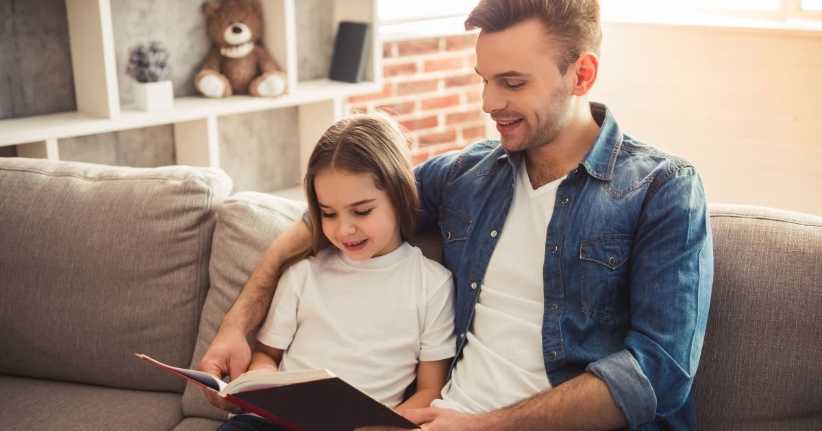Children reading book with parent